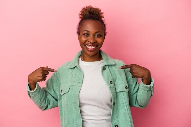 ピンクの背景に分離された若いアフリカ系アメリカ人女性は、指で下向き、前向きな気持ちです。