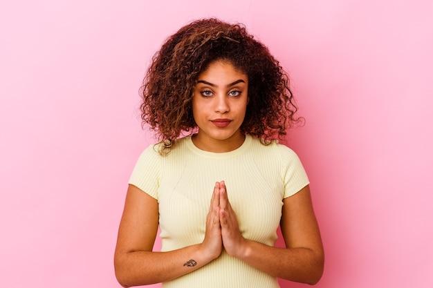 기도, 헌신, 신성한 영감을 찾고 종교적인 사람을 보여주는 분홍색 배경에 고립 된 젊은 아프리카 계 미국인 여자.