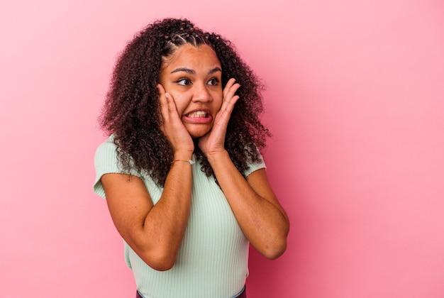 Молодая афро-американская женщина, изолированная на розовом фоне, испугалась и испугалась.