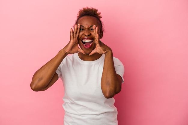 Молодая афро-американская женщина, изолированная на розовом фоне крича, возбуждена вперед.