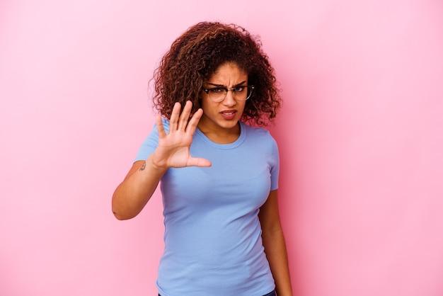ピンクの背景に分離された若いアフリカ系アメリカ人女性は、猫を模倣した爪、攻撃的なジェスチャーを示しています。