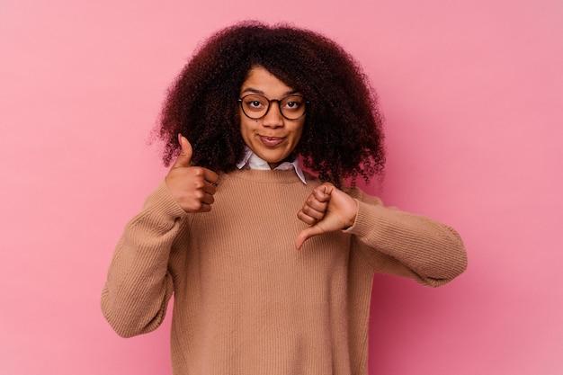 親指を上と親指を下に示すピンクの背景に分離された若いアフリカ系アメリカ人女性、難しい選択の概念