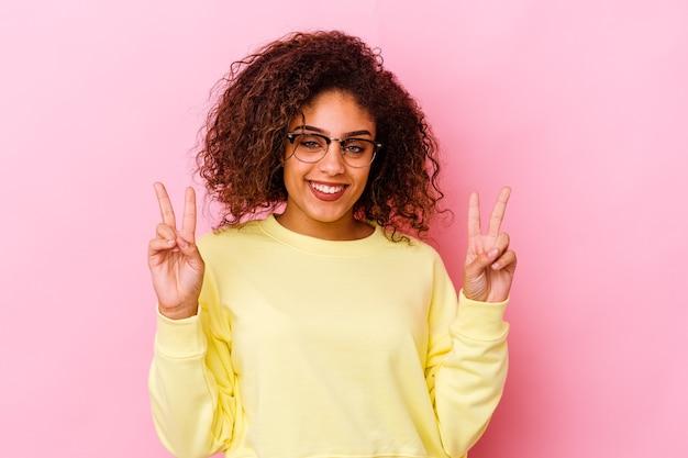 승리 기호를 표시 하 고 광범위 하 게 웃 고 분홍색 배경에 고립 된 젊은 아프리카 계 미국인 여자.