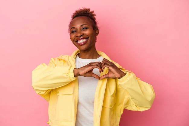 Молодая афро-американская женщина, изолированных на розовом фоне, улыбается и показывает форму сердца руками.