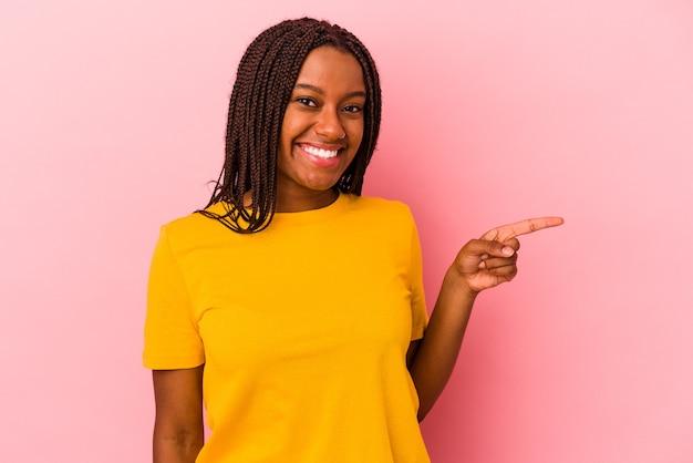 ピンクの背景に分離された若いアフリカ系アメリカ人の女性は、人差し指を離れて元気に指して微笑んでいます。