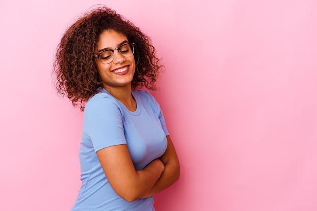 교차 팔 자신감 웃 고 분홍색 배경에 고립 된 젊은 아프리카 계 미국인 여자.