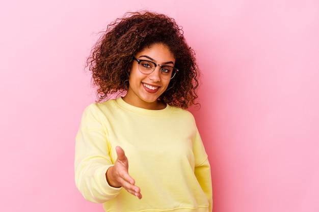 인사말 제스처에 카메라에 손을 스트레칭 분홍색 배경에 고립 된 젊은 아프리카 계 미국인 여자.