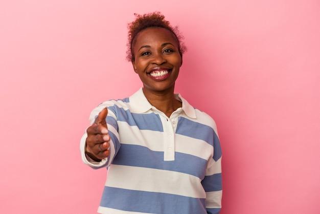 挨拶のジェスチャーでカメラで手を伸ばすピンクの背景に分離された若いアフリカ系アメリカ人女性。