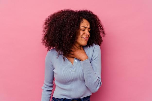 분홍색 배경에 고립 된 젊은 아프리카 계 미국인 여자는 바이러스 또는 감염으로 인해 목에 통증을 앓고 있습니다.
