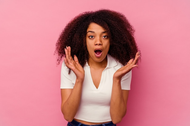 분홍색 배경에 고립 된 젊은 아프리카 계 미국인 여자 놀라게 하 고 충격.