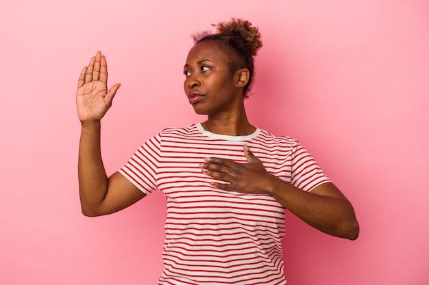 분홍색 배경에 격리된 젊은 아프리카계 미국인 여성이 가슴에 손을 얹고 맹세합니다.