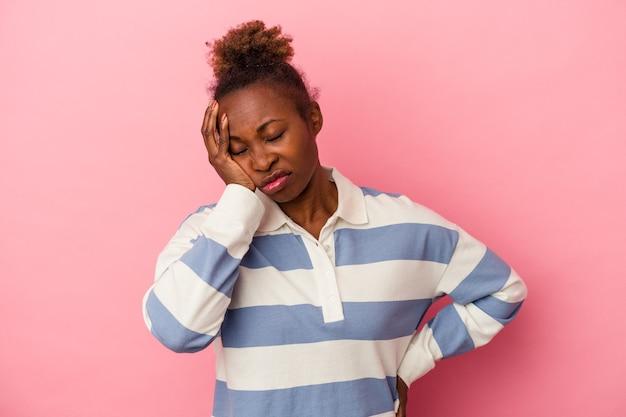 退屈、疲れ、リラックスした日を必要とするピンクの背景に孤立した若いアフリカ系アメリカ人の女性。