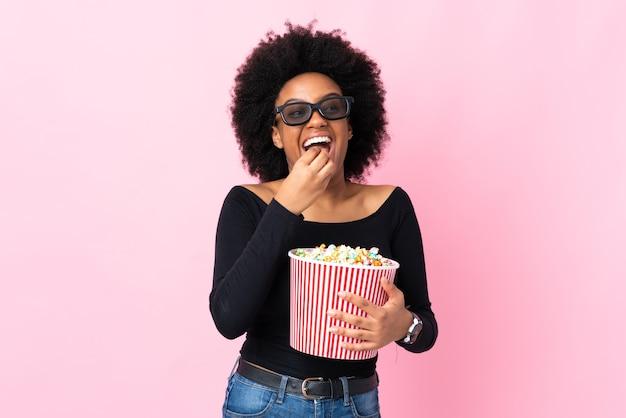 3dメガネとポップコーンの大きなバケツを保持してピンクの背景で隔離の若いアフリカ系アメリカ人女性