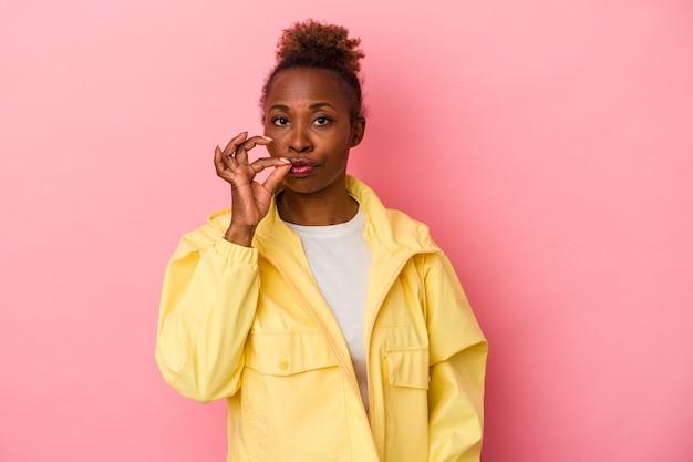 비밀을 유지하는 입술에 손가락으로 분홍색 배경에 고립 된 젊은 아프리카 계 미국인 여자.
