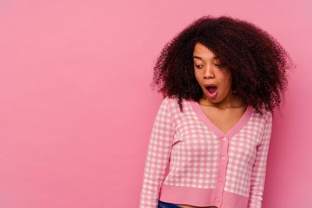 Молодая афро-американская женщина, изолированная на розовом, шокирована из-за чего-то, что она видела.