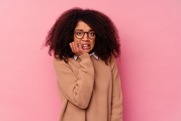 Молодая афро-американская женщина изолирована на розовых кусачих ногтях, нервничает и очень тревожится.