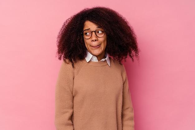 ピンクで孤立した若いアフリカ系アメリカ人の女性は混乱し、疑わしくて不安を感じています。