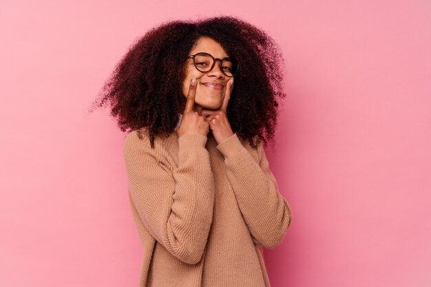 2つのオプションの間のピンクの疑いで孤立した若いアフリカ系アメリカ人の女性。