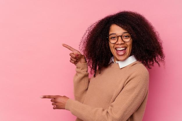 ピンクで孤立した若いアフリカ系アメリカ人の女性は、人差し指を離れて指差して興奮しました。