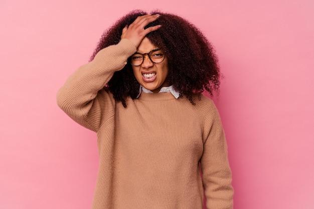 何かを忘れて、手のひらで額を叩き、目を閉じて、ピンクで孤立した若いアフリカ系アメリカ人の女性。