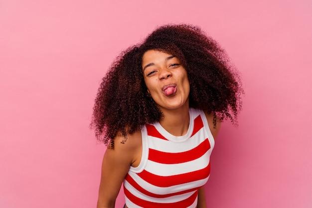 ピンクの面白いとフレンドリーな舌を突き出して孤立した若いアフリカ系アメリカ人の女性。
