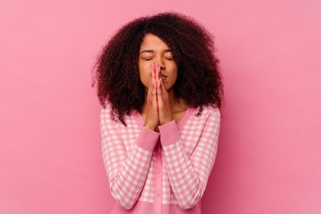 口の近くで祈って手をつないでピンクで隔離された若いアフリカ系アメリカ人の女性は、自信を持っています。