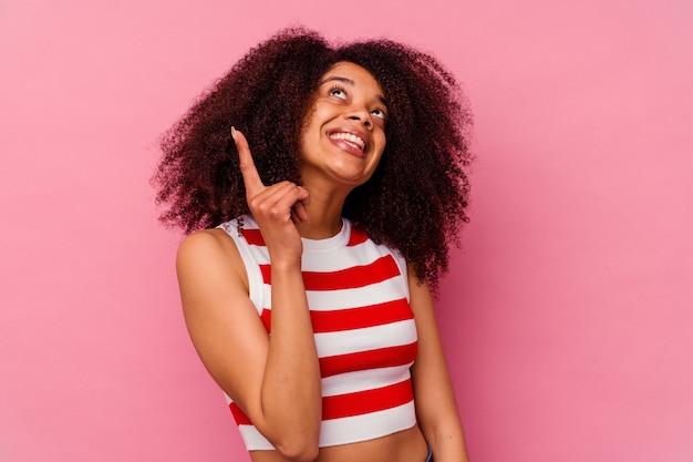 핑크에 고립 된 젊은 아프리카 계 미국인 여자는 빈 공간을 보여주는 두 앞 손가락으로 나타냅니다.
