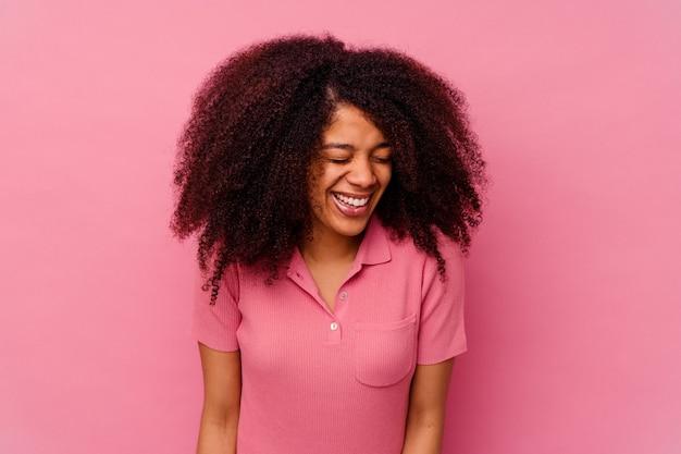 ピンクの笑いと目を閉じて孤立した若いアフリカ系アメリカ人の女性は、リラックスして幸せを感じます。