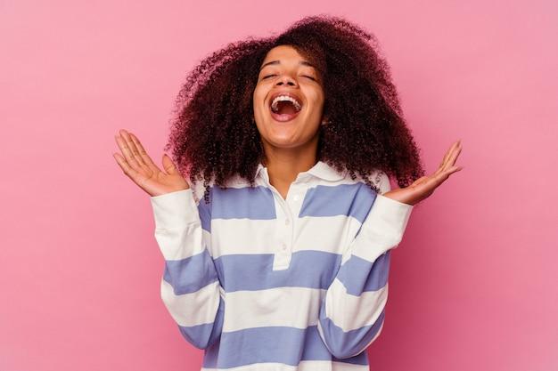 Молодая афро-американская женщина, изолированная на розовом, громко смеется, держа руку на груди.