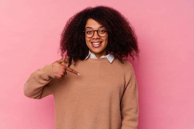 誇りと自信を持って、シャツのコピースペースを手で指しているピンクの人に孤立した若いアフリカ系アメリカ人の女性