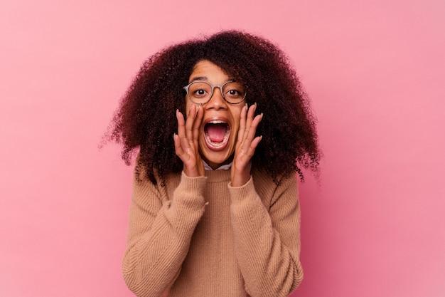 ピンクの叫びに孤立した若いアフリカ系アメリカ人の女性が正面に興奮しました。