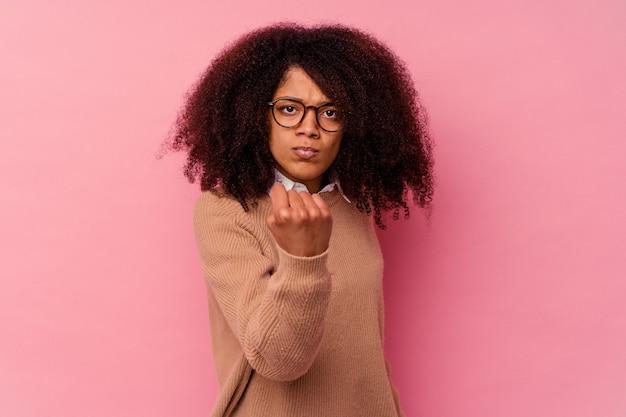 拳、攻撃的な表情を示すピンクで隔離の若いアフリカ系アメリカ人女性。
