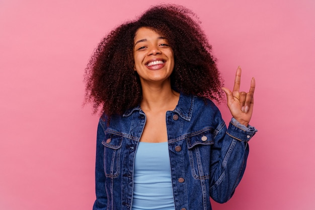 指でロックジェスチャーを示すピンクで隔離の若いアフリカ系アメリカ人女性