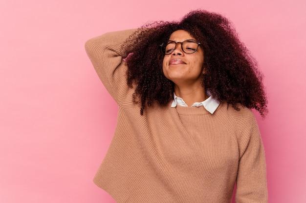 Молодая афро-американская женщина изолирована на розовом трогательном затылке, думая и делая выбор.