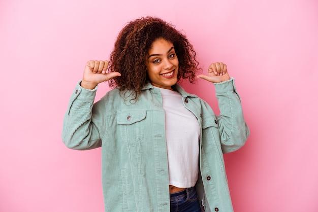 ピンクの壁に隔離された若いアフリカ系アメリカ人の女性は、誇りと自信を持って、従うべき例を感じます