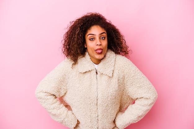 Молодая афро-американская женщина изолирована на розовой стене смешно и дружелюбно торчит языком.
