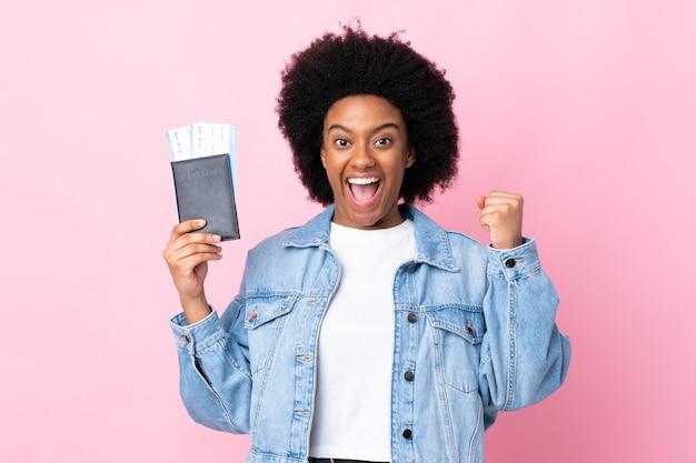 Молодая афро-американская женщина изолированная на розовой стене счастливая в каникулах с паспортом и билетами на самолет