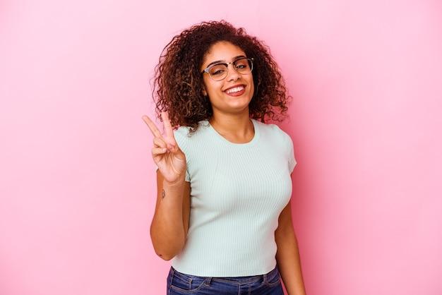 ピンクの壁に孤立した若いアフリカ系アメリカ人の女性は、指で平和のシンボルを示して楽しくてのんきです。