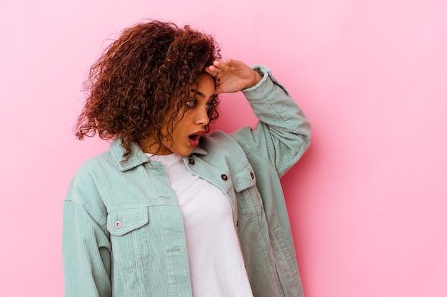 이마에 손을 멀리 유지 찾고 분홍색 벽에 고립 된 젊은 아프리카 계 미국인 여자.