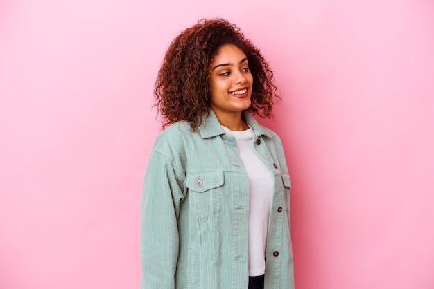 분홍색 벽에 고립 된 젊은 아프리카 계 미국인 여자는 옆으로 웃고, 밝고 쾌적한 보인다
