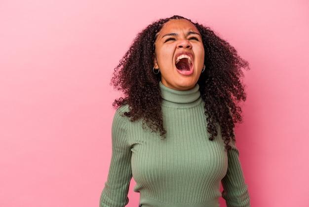 非常に怒っている、怒りの概念、欲求不満を叫んでピンクの壁に孤立した若いアフリカ系アメリカ人の女性。