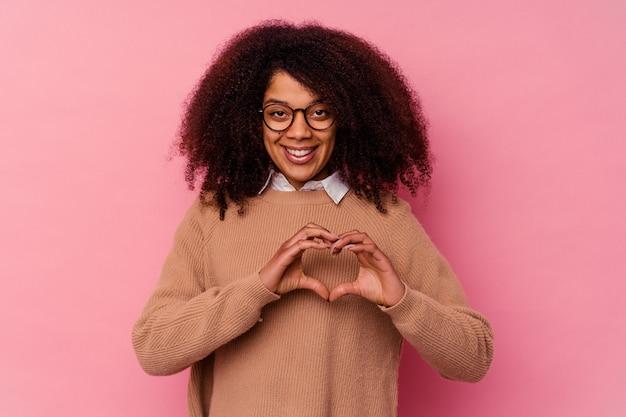 ピンクの壁に孤立した若いアフリカ系アメリカ人の女性は笑顔で手でハートの形を示しています。