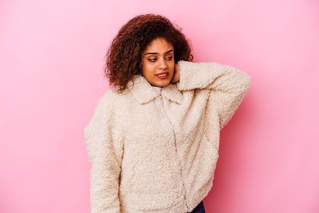 ピンクの壁に孤立した若いアフリカ系アメリカ人女性は疲れていて、頭に手を置いて非常に眠い