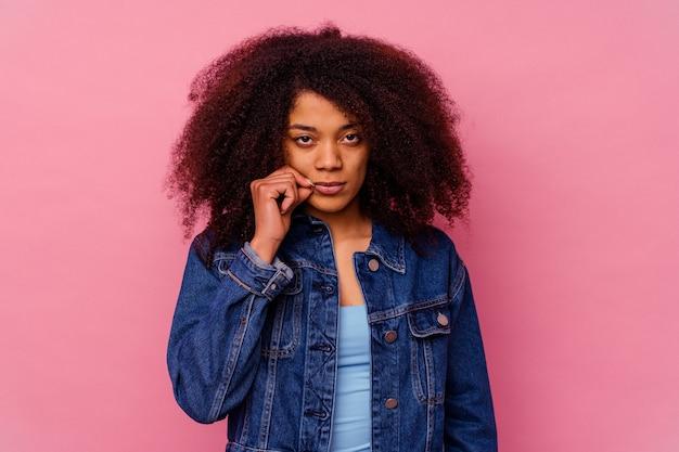 비밀을 유지하는 입술에 손가락으로 분홍색 벽에 고립 된 젊은 아프리카 계 미국인 여자.