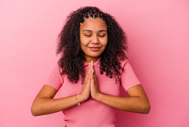 口の近くで祈る手でピンクの壁に隔離された若いアフリカ系アメリカ人の女性は、自信を持っています。