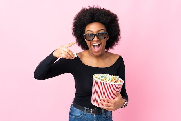 Молодая афроамериканская женщина изолирована на розовом в 3d-очках и держит большое ведро попкорна, указывая вперед