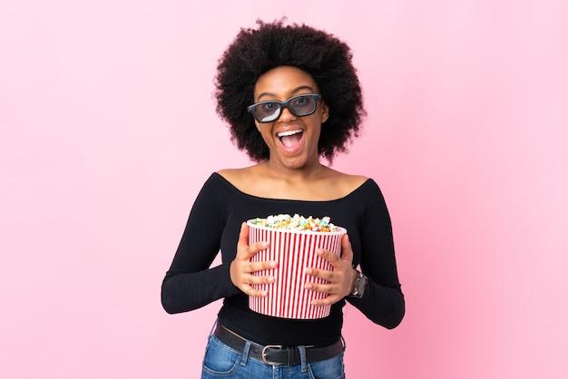 Молодая афроамериканка изолирована на розовом в 3d-очках и держит большое ведро попкорна