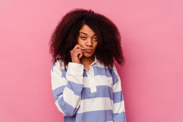 비밀을 유지하는 입술에 손가락으로 핑크에 고립 된 젊은 아프리카 계 미국인 여자.