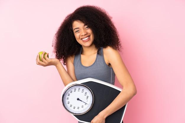 Молодая афро-американская женщина изолированная на пинке с весами и с яблоком