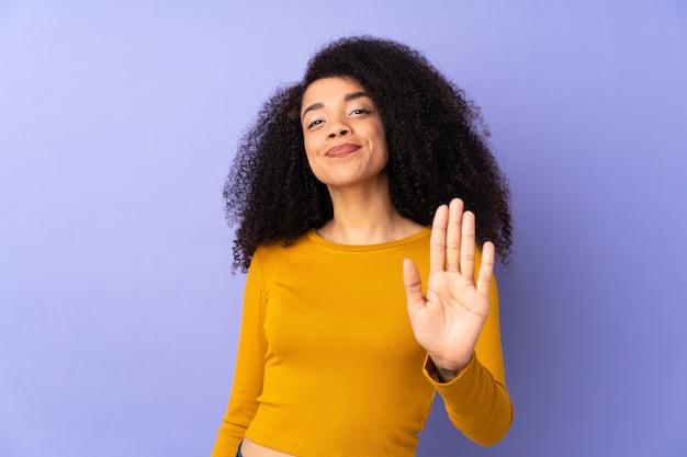 Молодая афро-американская женщина изолированная на пурпуре подсчитывая 5 с пальцами